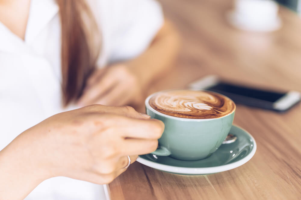 Coffee Cup on wooden table held by a woman