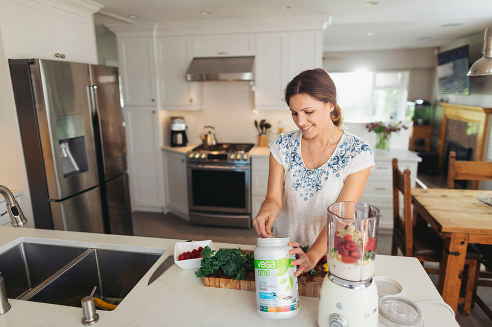 Woman making smoothie in a kitchen