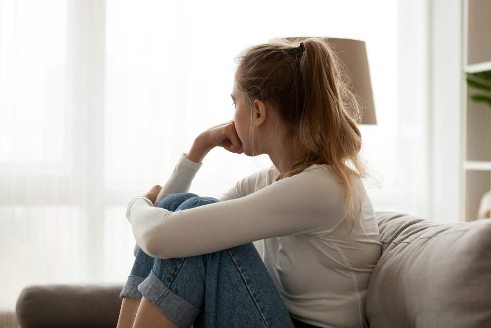 Somber young girl looking out window
