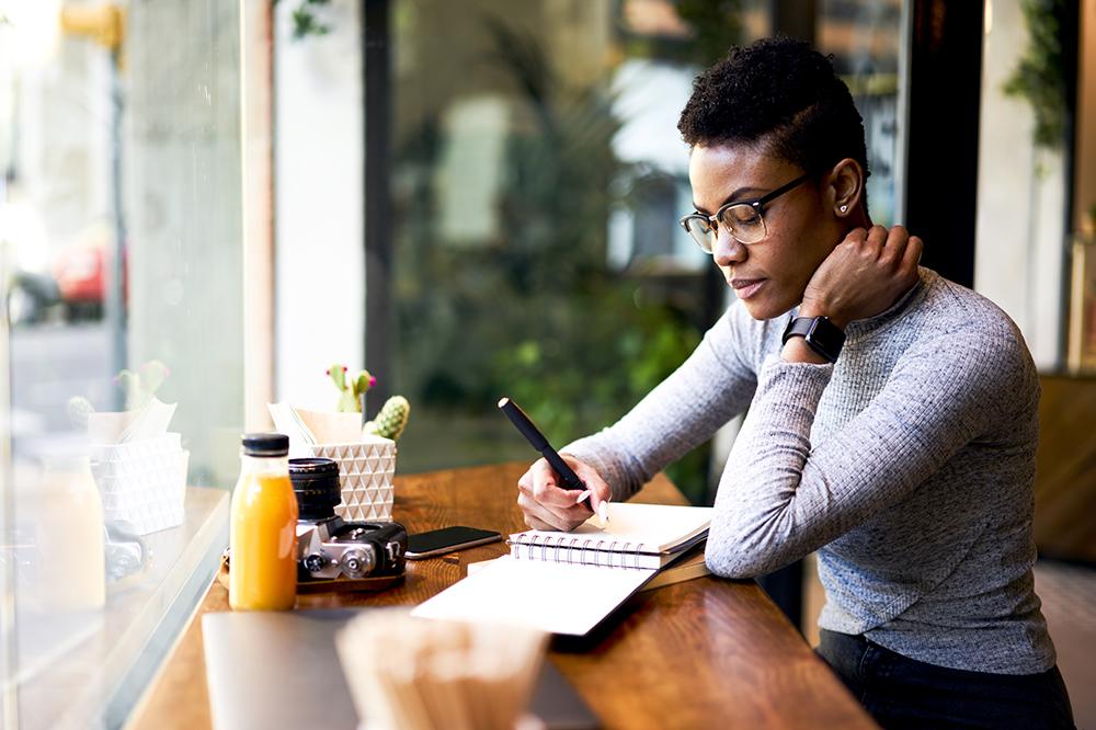 girl in coffee shop writing