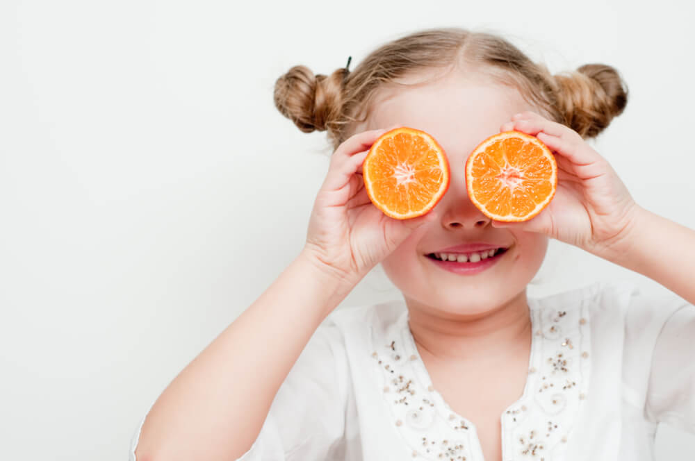 Young girl holding up orange slices to eyes