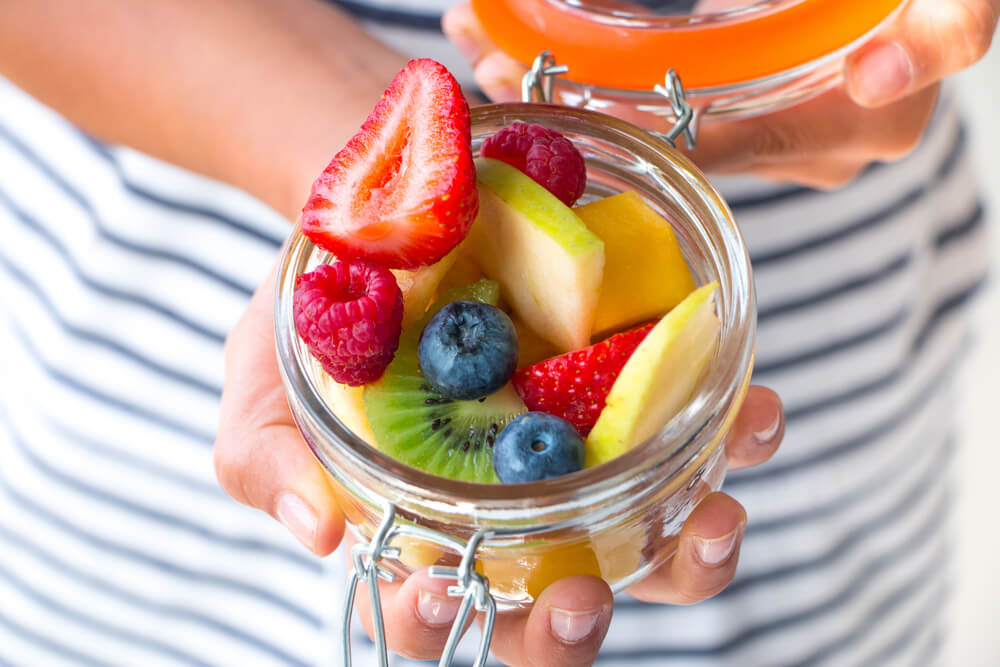 woman hold jar of fresh fruit as snack