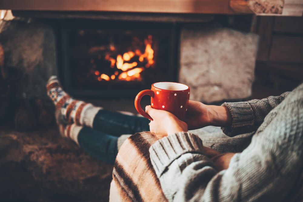 Person sitting by a fire drinking from a holiday mug