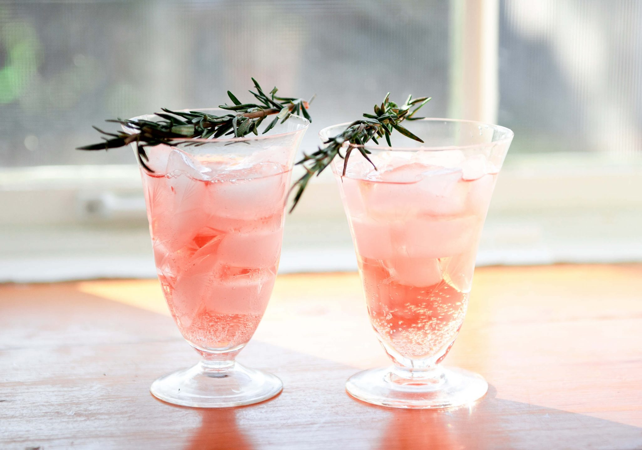 2 pink beverages garnished with rosemary