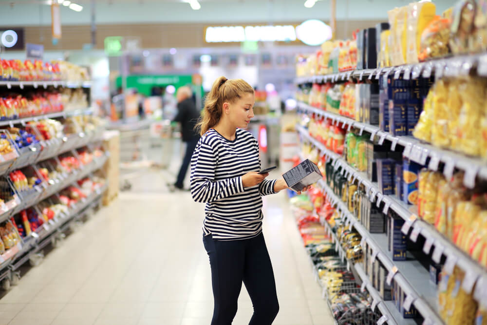woman in grocery store looking at food label