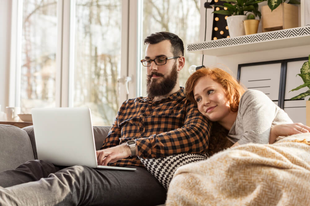 couple in a cozy blanket watching a movie