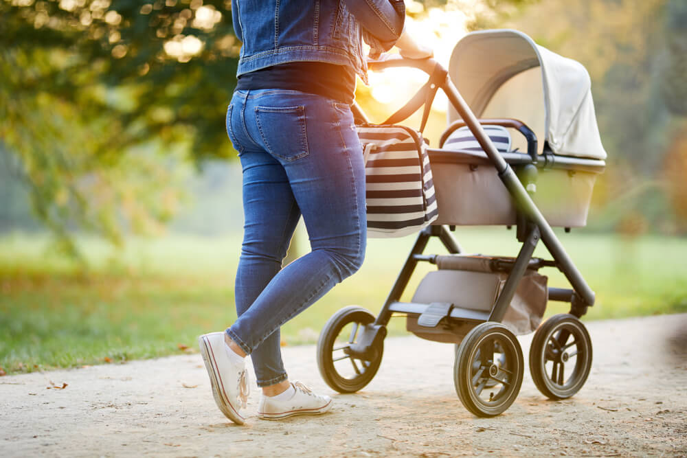 Mom walking with Baby in stroller in the spring time