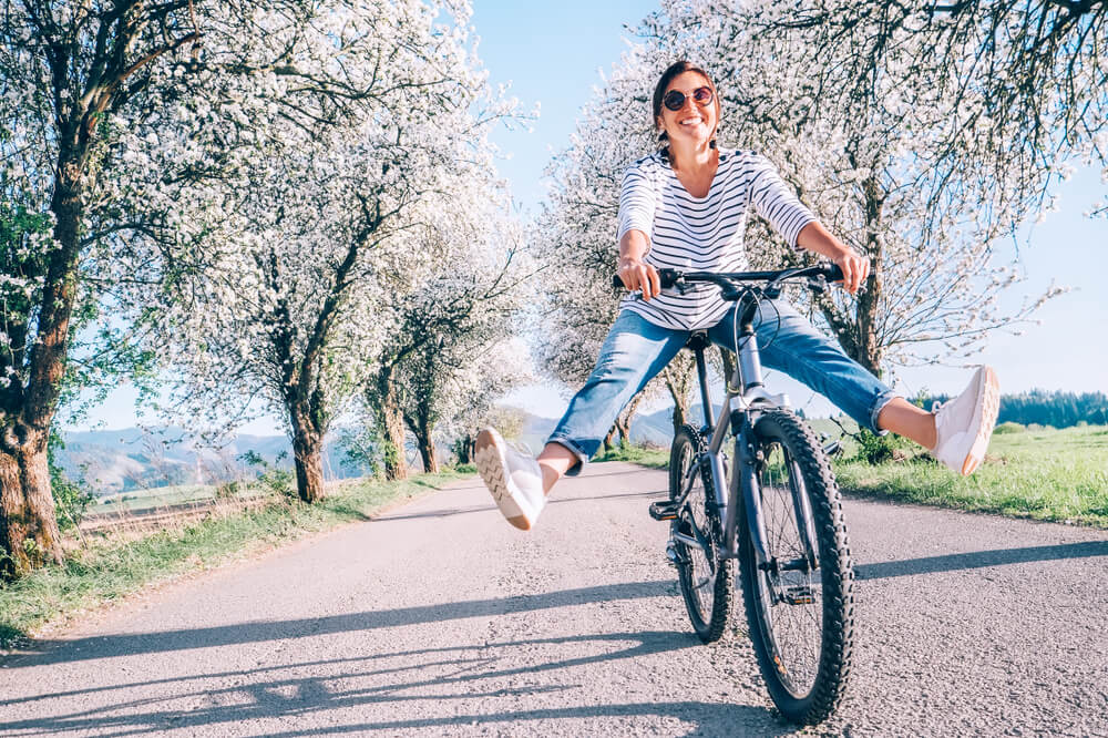 happy woman riding bike during the spring