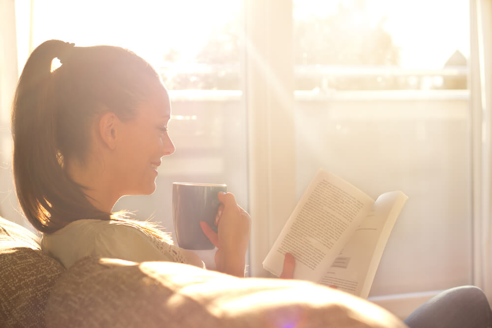 woman reading on couch with sun coming in window