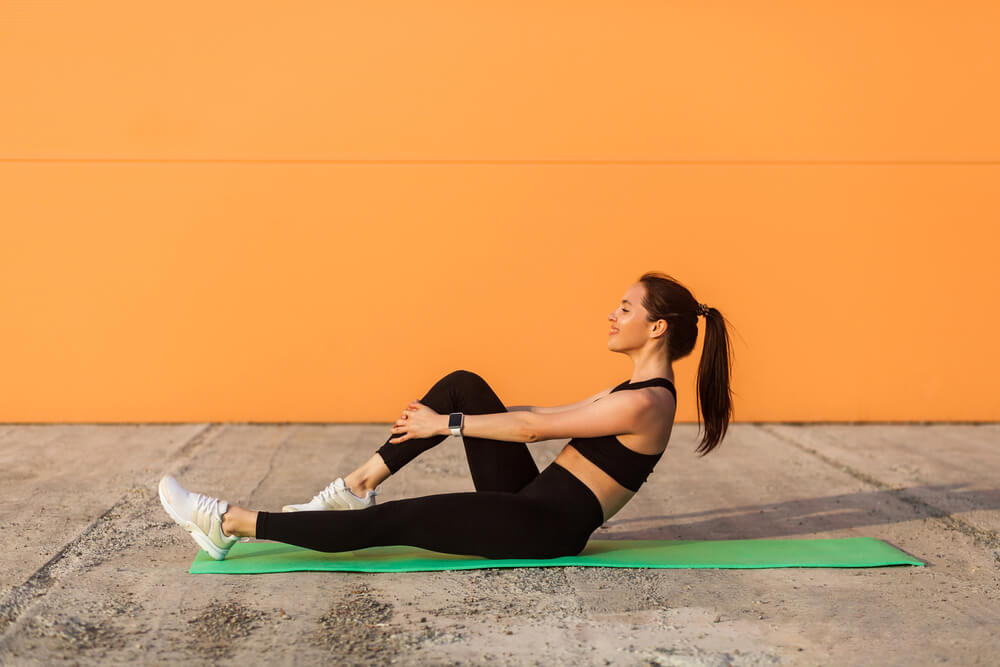 Woman working out outside near an orange wall