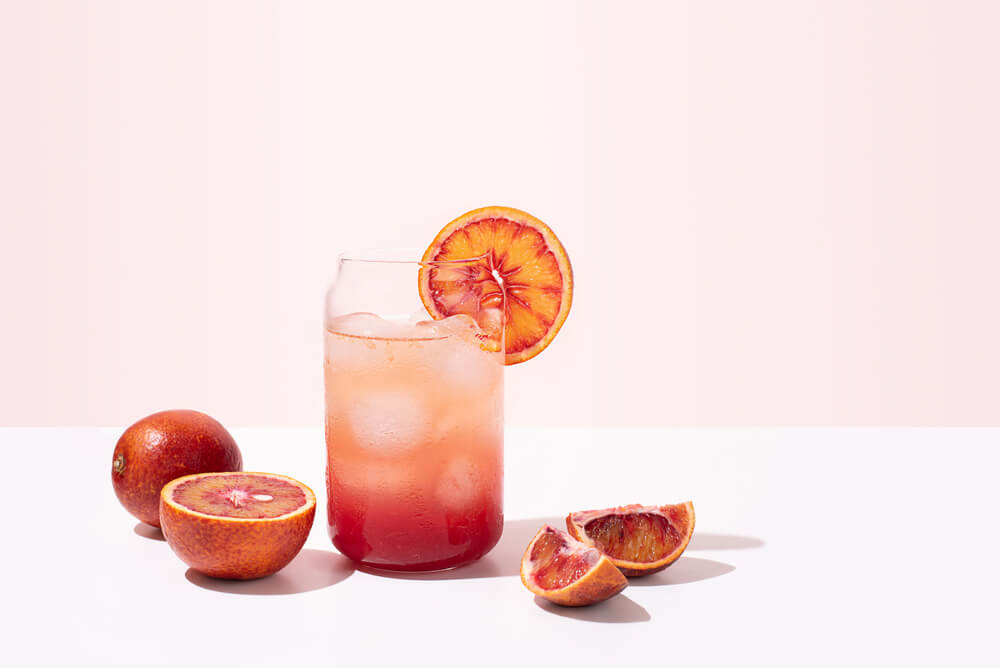 colourful beverage with slices of blood orange around it